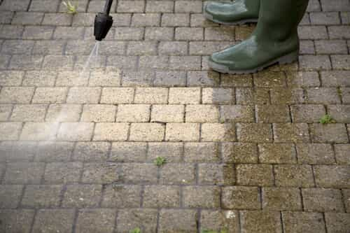 person using power washer on stone walkway